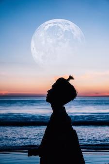 Retrato dramático, vista lateral de la silueta del hombre en la playa, la luna fue proporcionada por