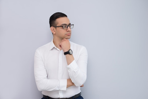 Retrato del ejecutivo joven pensativo que se coloca con la mano en la barbilla