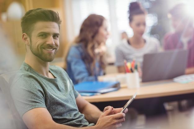 Retrato del ejecutivo de operaciones de sexo masculino que sostiene la tableta digital