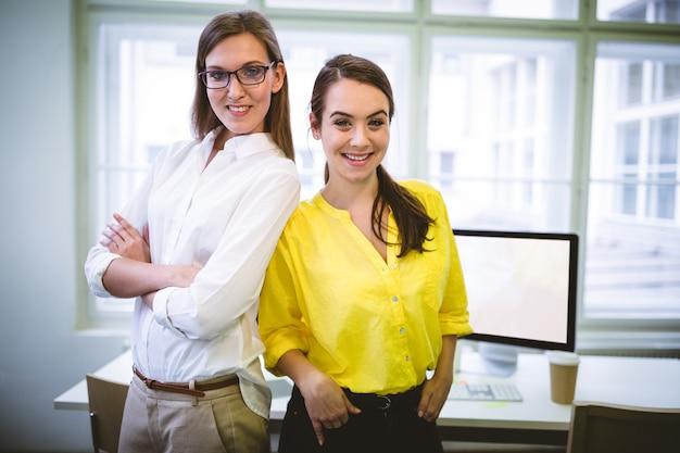 Retrato de ejecutivos felices de pie en la oficina creativa