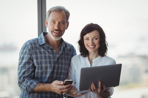 Retrato de ejecutivos de negocios que usan teléfonos móviles y computadoras portátiles