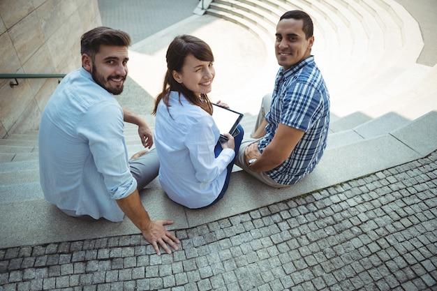 Retrato de ejecutivos sentados con tableta digital en las escaleras