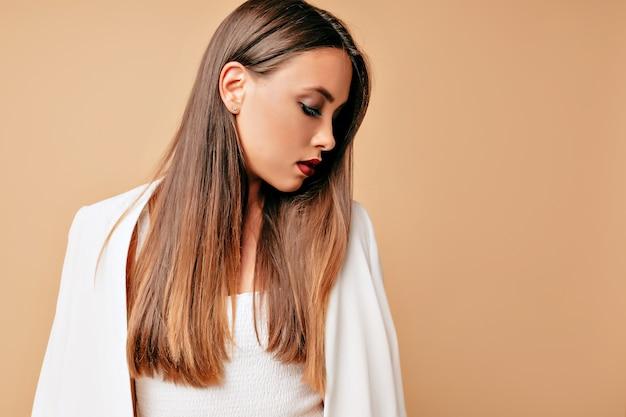 Retrato de elegante adorable joven bella mujer, aislada sobre pared beige, mirando de perfil, mirada concentrada.