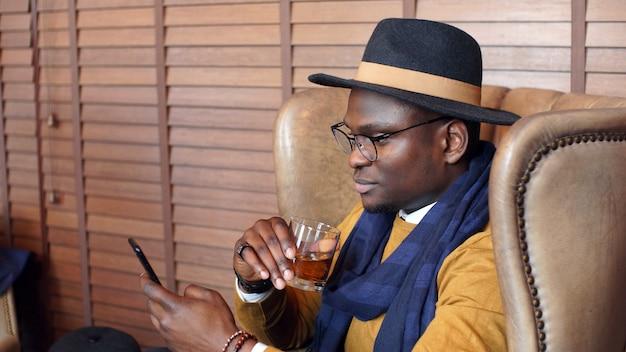 Retrato de un elegante hombre afroamericano en un sombrero y gafas, sentado en una silla mirando un teléfono inteligente y bebiendo whisky, coñac, bebida fuerte