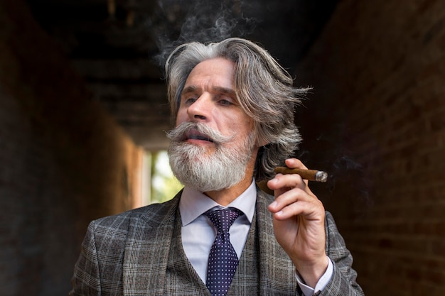 Retrato de elegante hombre maduro fumando puros cubanos