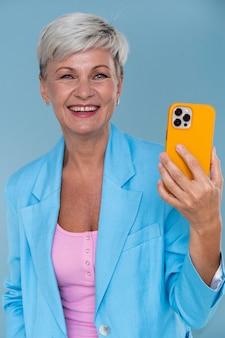Retrato, de, elegante, mujer mayor, tenencia, ella, teléfono