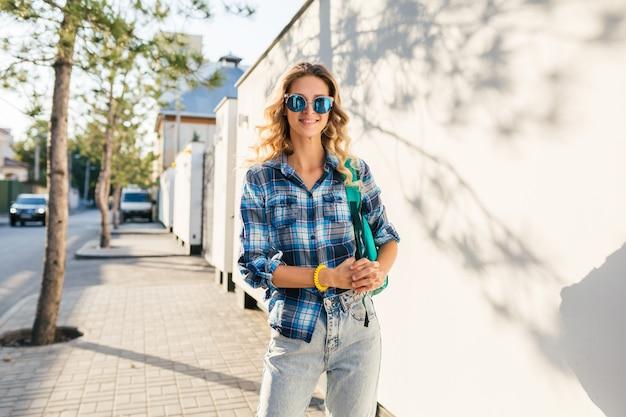 Retrato de elegante mujer rubia feliz sonriente caminando en la calle con camisa azul