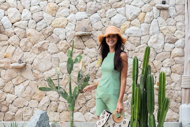 Retrato de elegante mujer sonriente linda feliz en elegante vestido verde de verano con bolsa con sombrero de paja sobre fondo de pared de piedra blanca y cactus
