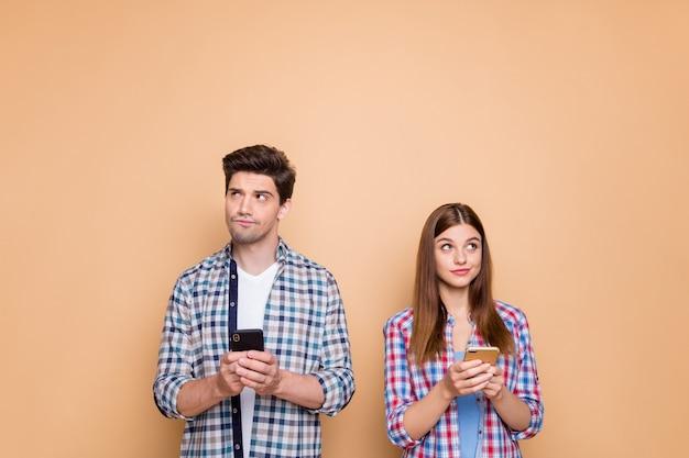 Retrato de él, ella, bonita pareja pensativa de mente atractiva vistiendo camisa a cuadros creando nuevos medios de comunicación en línea de internet smm aislados sobre fondo de color beige pastel