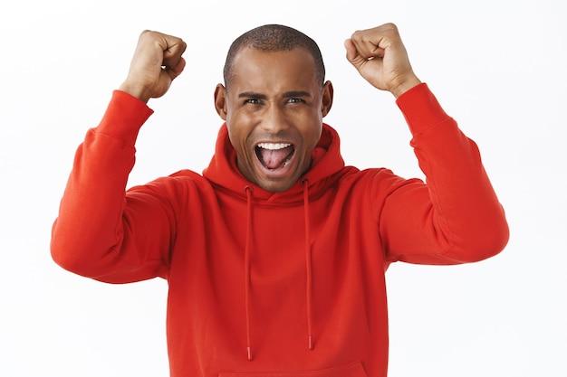 Retrato de emocionado, feliz regocijo hombre afroamericano levanta las manos en señal de triunfo, gritando sí, sí como viendo un juego de deportes, apuesta ganadora