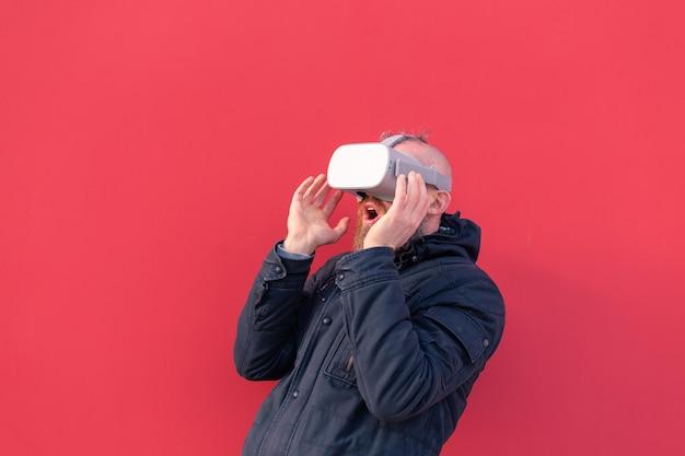 Retrato emocional de un hombre en la calle con gafas de realidad con el telón de fondo de una pared roja
