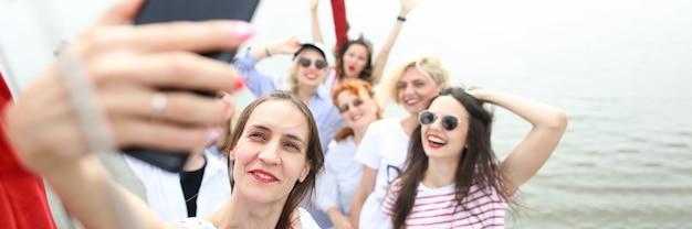 Retrato de empresa alegre tomando selfie en smartphone. amigos felices fiesta en yate