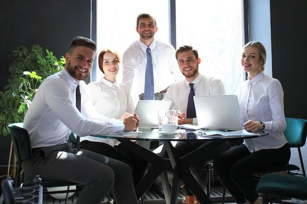 Retrato de una empresa positiva empleados en una reunión de negocios de oficina.