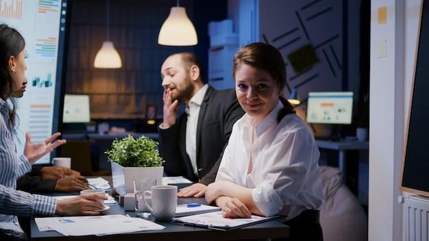 Retrato de empresaria adicta al trabajo mirando a la cámara mientras trabajaba en la sala de reuniones de la oficina de la empresa