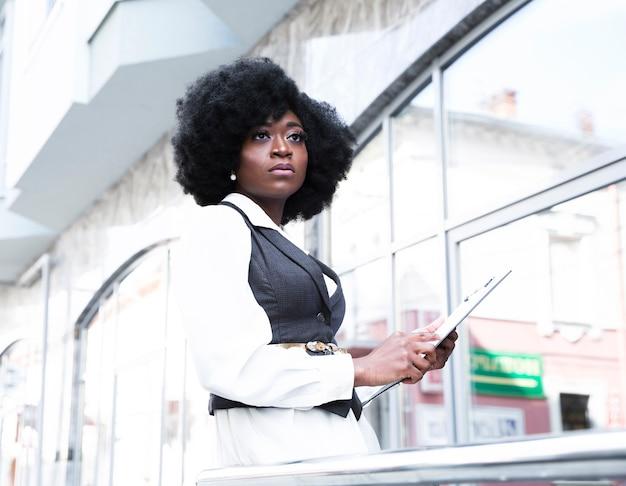 Retrato de la empresaria africana joven que sostiene el tablero que mira lejos