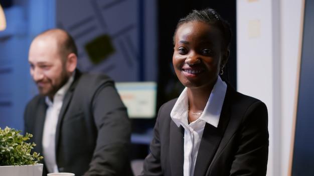 Retrato de la empresaria afroamericana escribiendo la estrategia de la empresa en el portátil