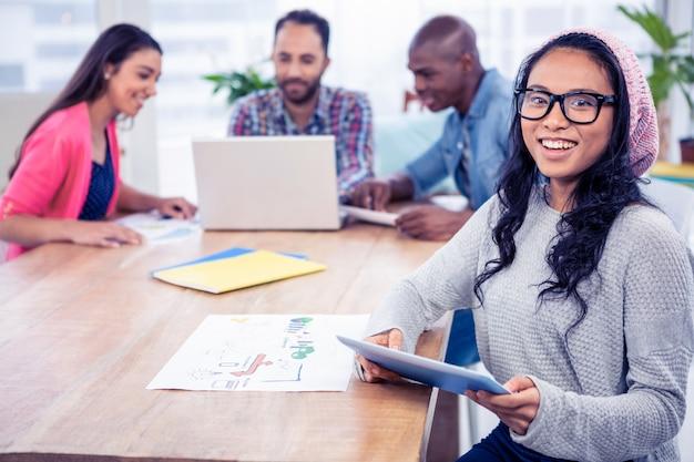 Retrato de la empresaria alegre que sostiene la tableta digital mientras que se sienta con los colegas en oficina