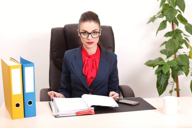 El retrato de la empresaria con la computadora portátil escribe en un documento en su oficina
