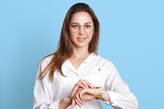 El retrato de la empresaria confiada joven sonriente en vidrios de moda, distribuye su tiempo cuidadosamente, bueno en la gestión del tiempo. modelo delgado de pelo largo posa con blusa blanca y falda negra.