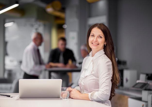 Retrato de la empresaria confiada con el ordenador portátil y el vidrio de agua en el lugar de trabajo