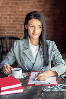 Retrato de una empresaria está escribiendo en blanco en blanco mientras sostiene una taza de café en el café