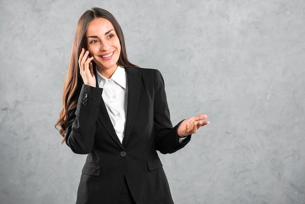 Retrato de una empresaria feliz joven que gesticula mientras que habla en el teléfono móvil contra el contexto gris