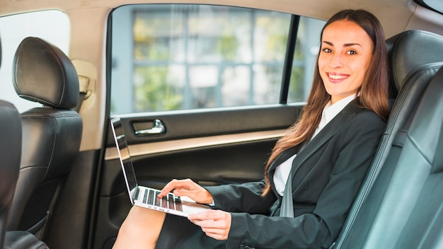 Retrato de una empresaria feliz que se sienta dentro del coche usando la computadora portátil