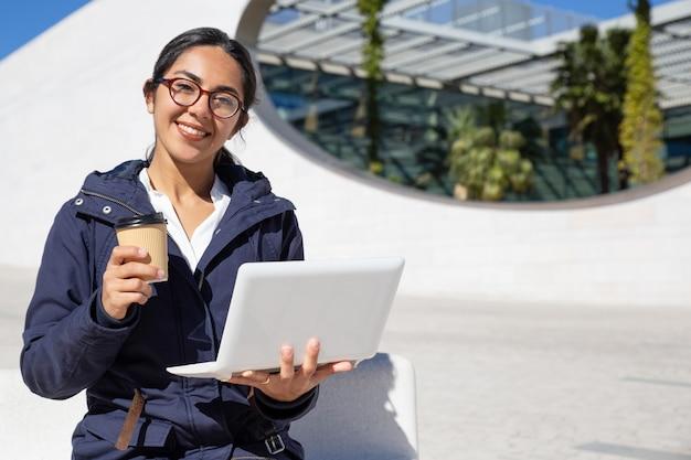 Retrato de la empresaria feliz que tiene descanso para tomar café al aire libre