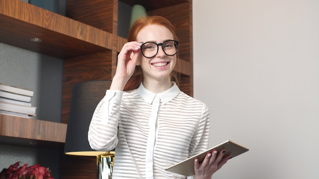 Retrato de la empresaria feliz con la tableta en la habitación.