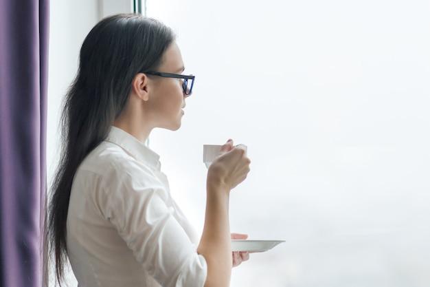Retrato de empresaria en gafas de camisa blanca con una taza de café