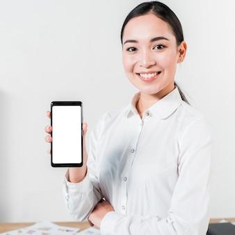 Retrato de una empresaria joven asiática sonriente que muestra el teléfono móvil de la pantalla en blanco