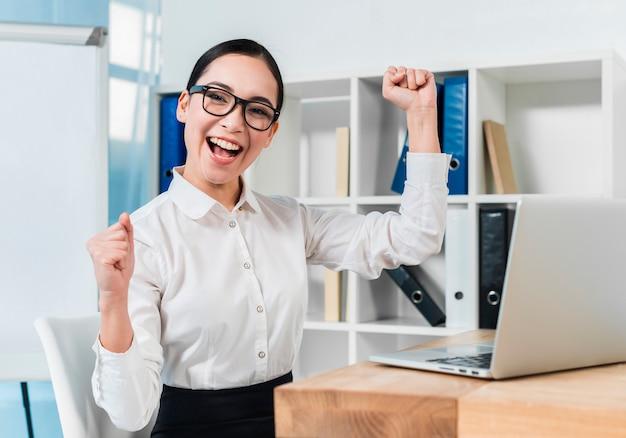 Retrato de una empresaria joven emocionada que anima en el lugar de trabajo