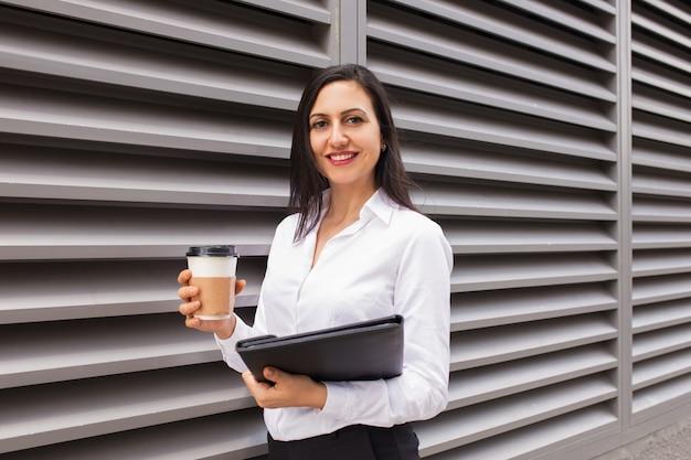 Retrato de la empresaria joven feliz con café para llevar