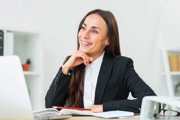 Retrato de la empresaria joven feliz que se sienta en el lugar de trabajo que sueña despierto