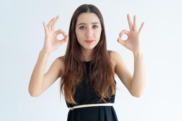Retrato de la empresaria joven positiva que muestra la muestra aceptable