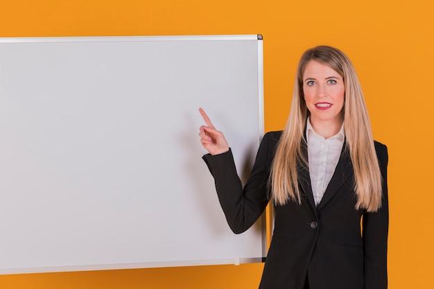 Retrato de una empresaria joven que señala su dedo en whiteboard contra un fondo anaranjado