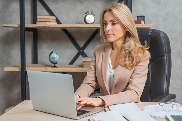 Retrato de una empresaria joven que se sienta en el lugar de trabajo usando el ordenador portátil en oficina