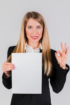 Retrato de una empresaria joven que sostiene el libro blanco en la mano que muestra la muestra aceptable