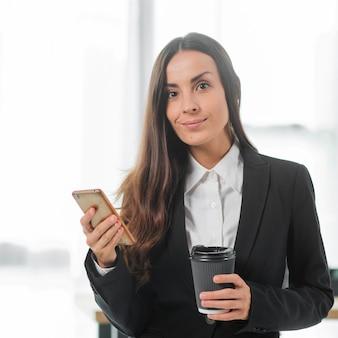 Retrato de la empresaria joven que sostiene smartphone y la taza de café disponible en manos