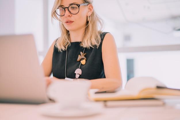Retrato de una empresaria joven rubia que mira la computadora portátil en la oficina Foto gratis