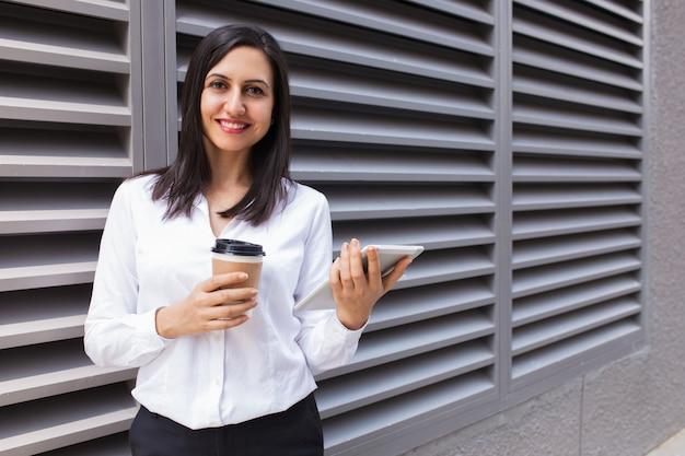 Retrato de la empresaria joven sonriente con café y panel táctil