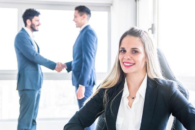 Retrato de la empresaria joven sonriente delante de los hombres que sacuden las manos
