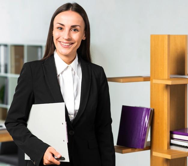 Retrato de la empresaria joven sonriente que se coloca en la oficina