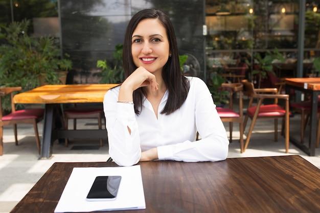 Retrato de la empresaria joven sonriente que se sienta en la tabla