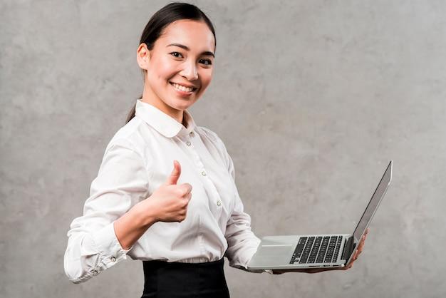 Retrato de una empresaria joven sonriente que sostiene el ordenador portátil a disposición que muestra el pulgar encima de la muestra