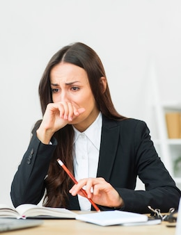Retrato de la empresaria joven triste que sostiene el lápiz rojo en su mano que llora