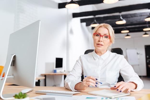 Retrato de una empresaria madura seria que trabaja en la oficina con la computadora