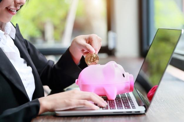 Retrato de empresaria mostrando bitcoin o moneda en piggy rosa.