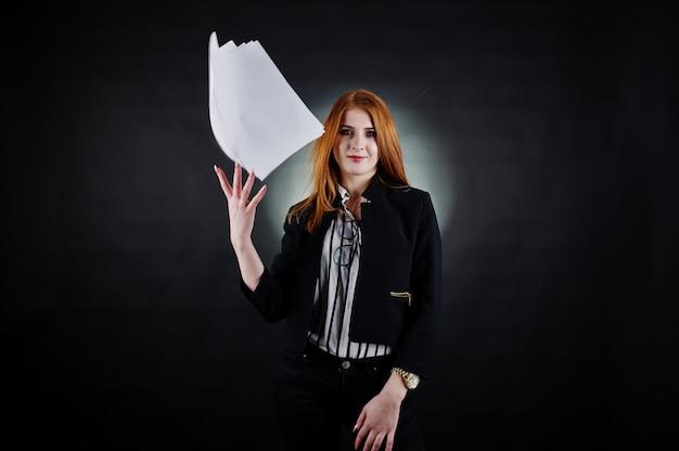Retrato de una empresaria pelirroja en blusa a rayas y chaqueta tirando el papel.