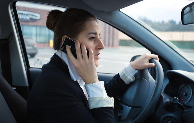 Retrato de empresaria preocupada conduciendo coche y hablando por teléfono
